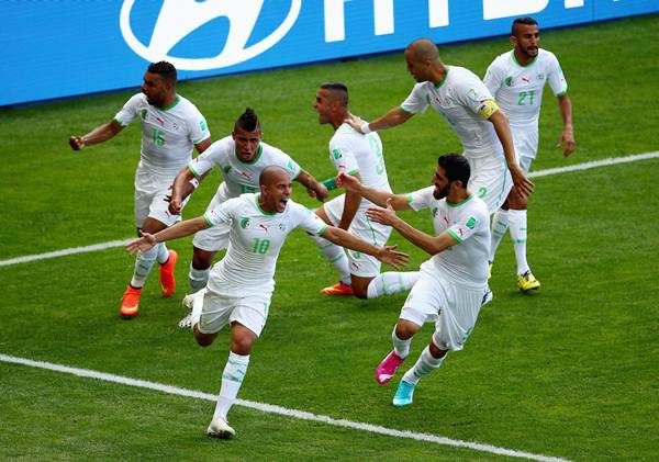 Sofiane Feghouli (No 10) of Algeria celebrates with his teammates after scoring his team's first goal from a penalty kick