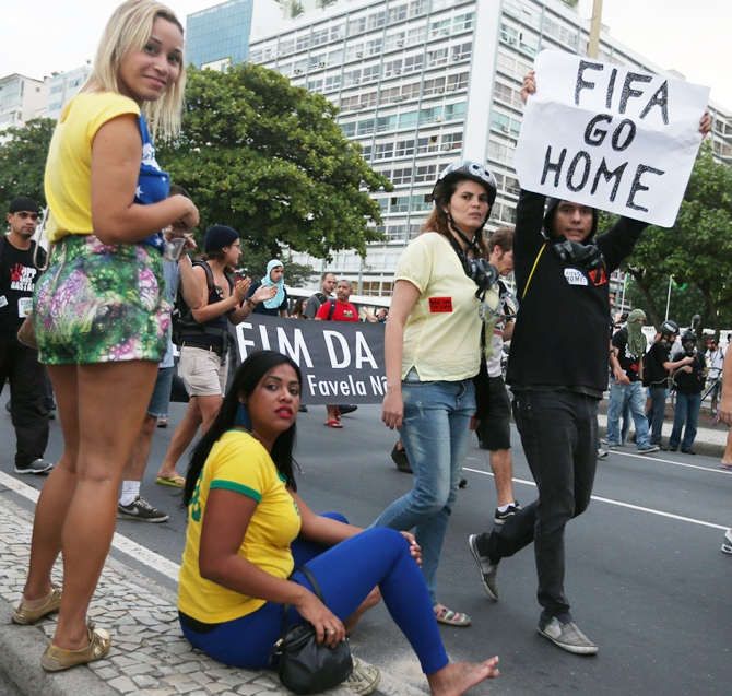 A protestor holds a 'FIFA Go Home' sign during an anti-World Cup demonstration in the Copacabana section