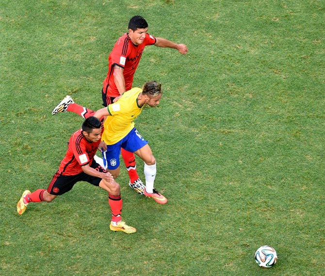 Neymar of Brazil takes on Jose Juan Vazquez of Mexico and Francisco Javier Rodriguez