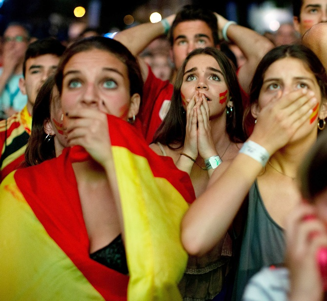 Spanish fans react while watching their team play against the Chileans