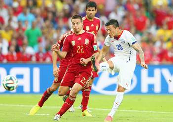 Charles Aranguiz of Chile shoots and scores his team's second goal against Cesar Azpilicueta of Spain