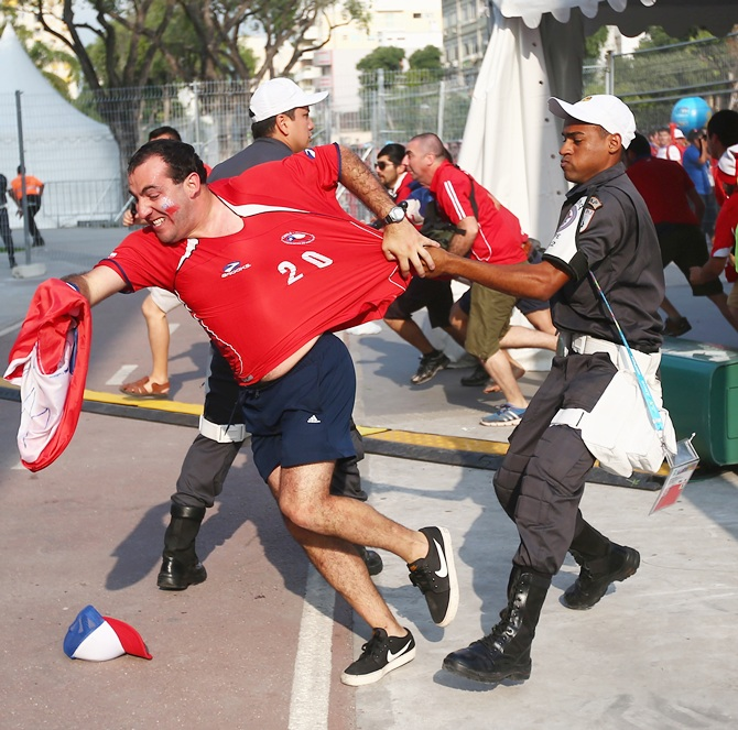 Security personnel attempt to control Chilean fans outside the stadium