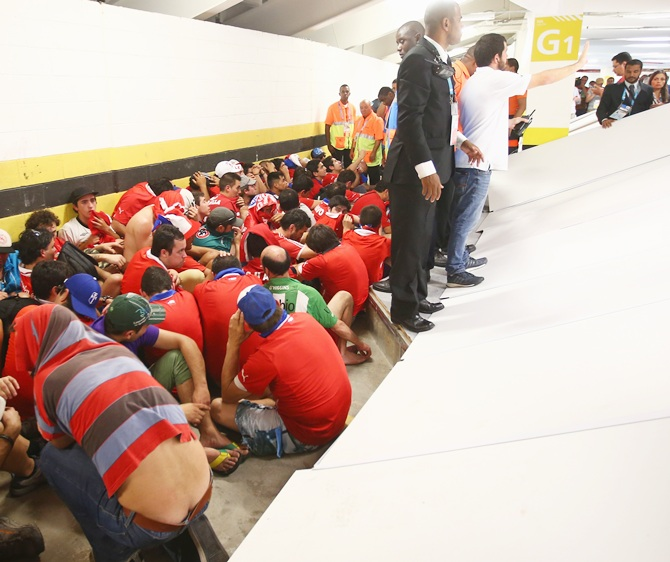 Security personnel attempt to control fans after breaking through security and   attempting to enter the stadium prior to the 2014 FIFA World Cup