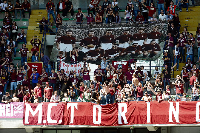 Supporters of Torino FC hold a banners commemorating the Torino players who lost their lives when their plane crashed in what is known as the Superga air disaster, on the 65th anniversary of the tragedy during the Serie A match between AC Chievo Verona and Torino FC at Stadio Marc'Antonio Bentegodi on May 4, 2014 in Verona, Italy