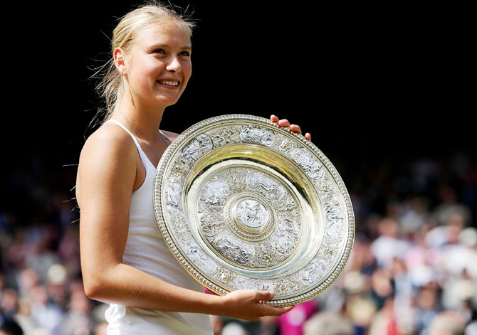 Maria Sharapova of Russia poses with her trophy after she won against Serena Williams of USA in the ladies final match at the Wimbledon Lawn Tennis Championship on July 3, 2004