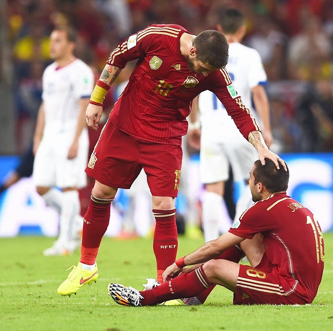 Sergio Ramos of Spain consoles Jordi Alba after the 2-0 defeat to Chile in the 2014 FIFA World Cup Brazil Group B match