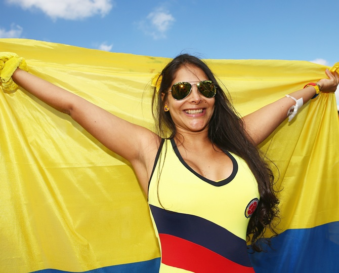 A Colombia fan holds a flag prior to the 2014 FIFA World Cup Brazil Group C match against Ivory Coast; (inset) Pablo Escobar