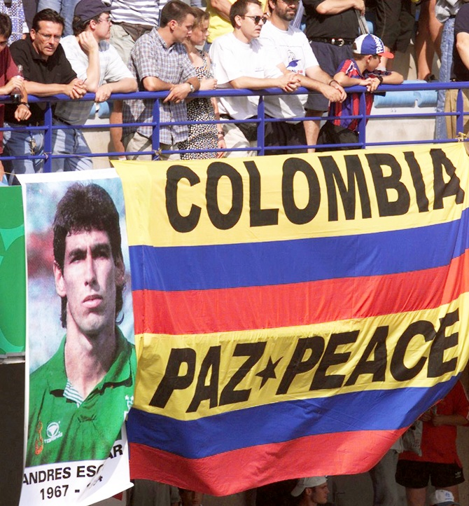 Colombian supporters watch the first round World Cup match between Colombia and Tunisia over a Colombian flag with the inscription: 'Colombia-Peace,' placed next to a portrait of player Andres Escobar in Montpellier