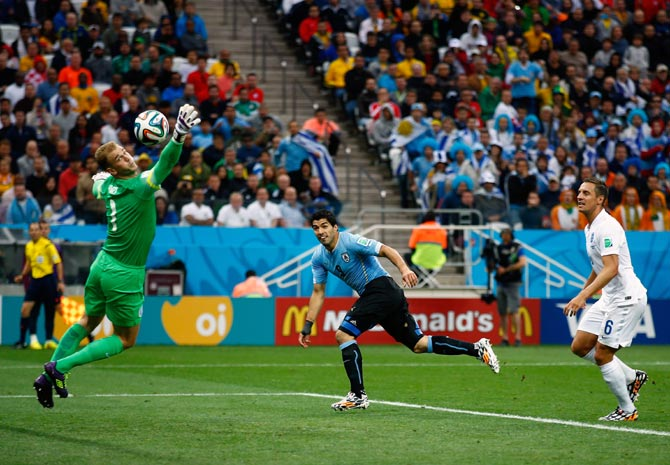 Luis Suarez of Uruguay scores his team's first goal past England goalkeeper Joe Hart