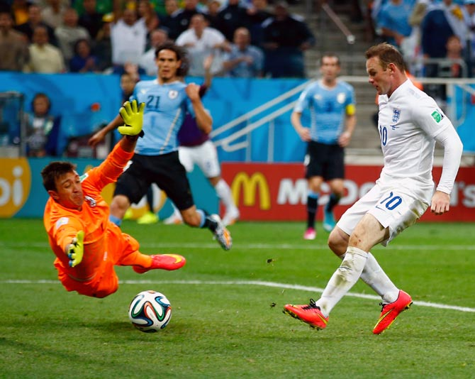 Wayne Rooney of England scores his team's first goal past Uruguay goalkeeper Fernando Muslera