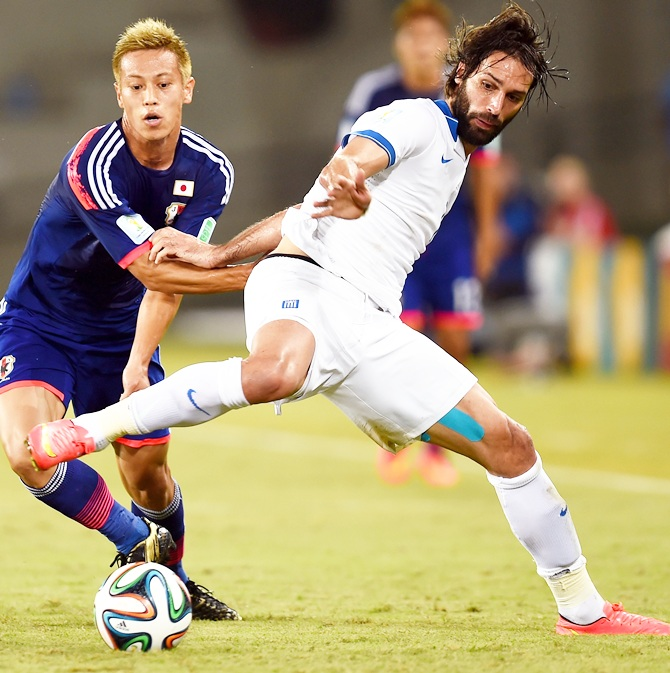 Giorgos Samaras of Greece competes for the ball with Keisuke Honda of Japan