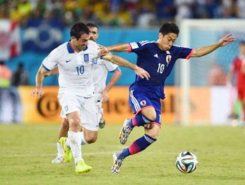 Giorgos Karagounis of Greece challenges Shinji Kagawa of Japan
