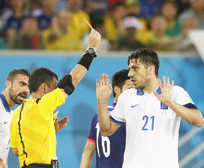 Greece's Kostas Katsouranis, right, is shown a red card by referee Joel Aguilar of El Salvador