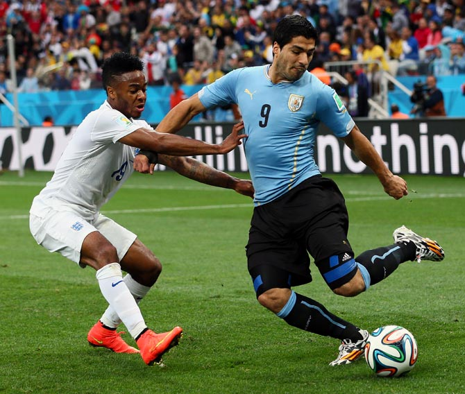 Luis Suarez, right, tries to get the ball past Raheem Sterling of England