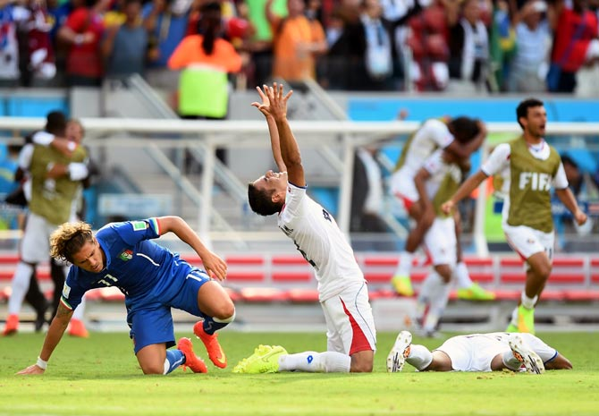 Michael Umana of Costa Rica (centre) celebrates after winning the match against Italy