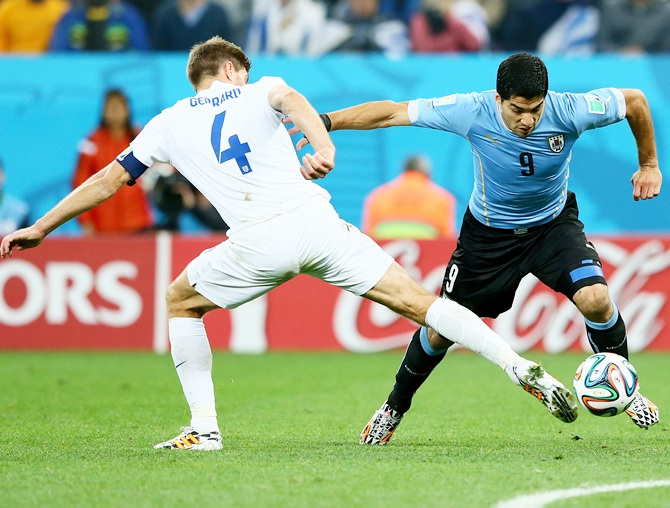 Steven Gerrard of England and Luis Suarez of Uruguay compete for the ball