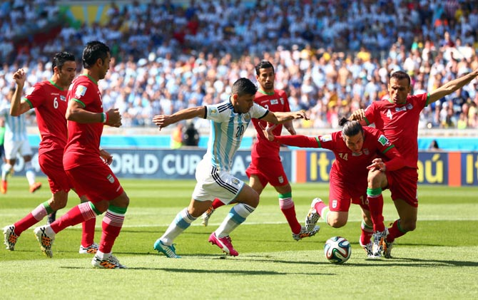 Sergio Aguero of Argentina tries to get the ball past Iran's defenders