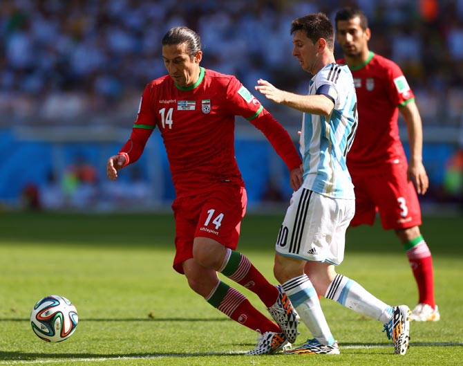 Andranik Teymourian of Iran (left) challenges Lionel Messi