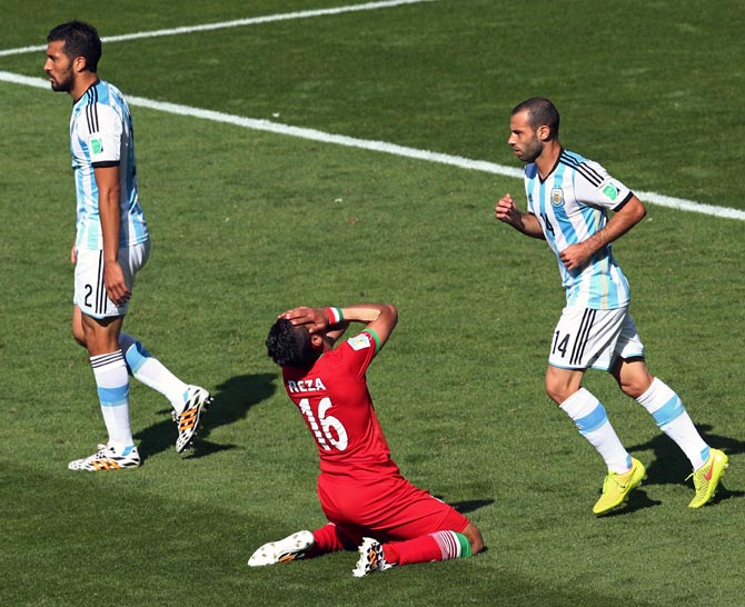 Reza Ghoochannejhad (centre) of Iran reacts after a missed chance