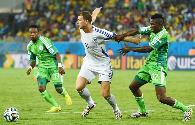 Edin Dzeko of Bosnia and Herzegovina and Kenneth Omeruo of Nigeria compete for the ball during their match on Friday