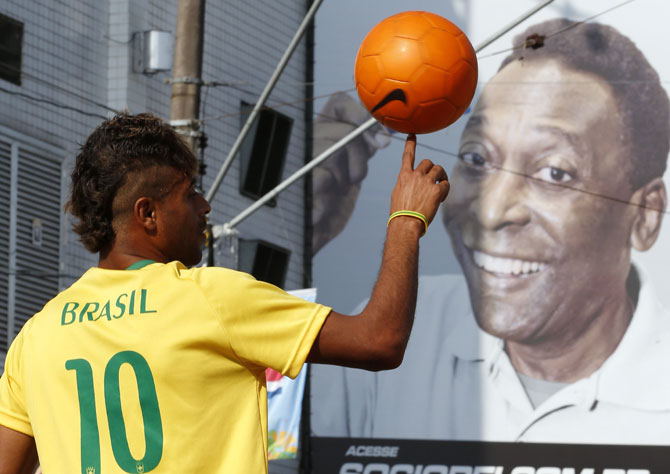 Thiago Silva plays with a soccer ball in front of Brazil's Santos soccer team stadium where soccer legend Pele played during his career