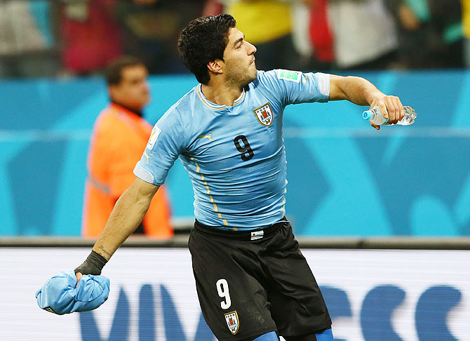 Luis Suarez of Uruguay throws a shirt into the crowd after defeating England