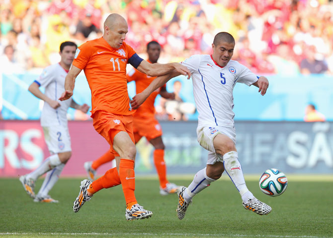Francisco Silva of Chile controls the ball against Arjen Robben of the Netherlands