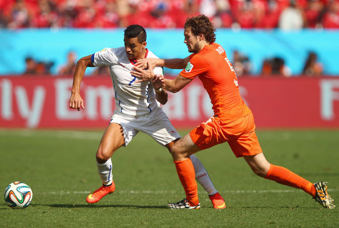 Alexis Sanchez of Chile and Daley Blind of the Netherlands compete for the ball