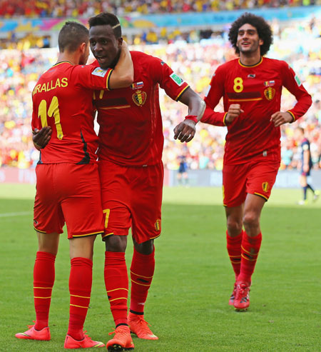 Divock Origi of Belgium, center, celebrates scoring his team's first goal with Kevin Mirallas