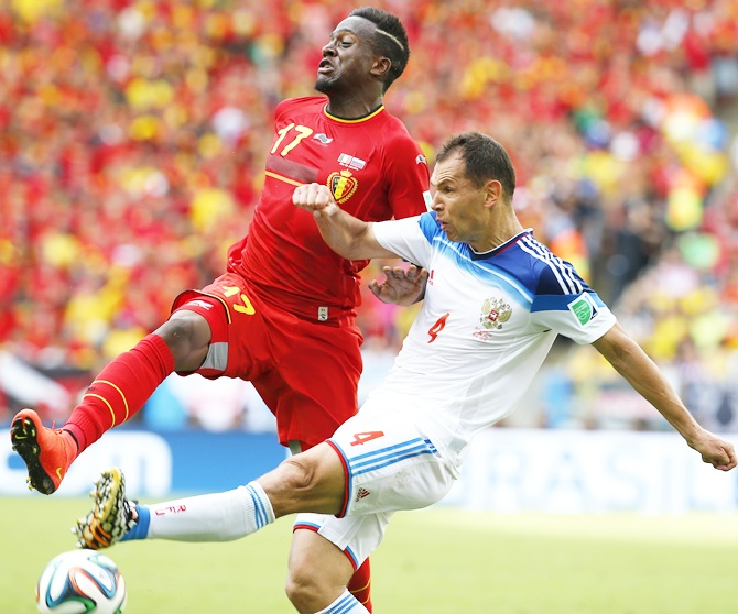 Belgium's Divock Origi, left, fights for the ball with Russia's Sergey Ignashevich