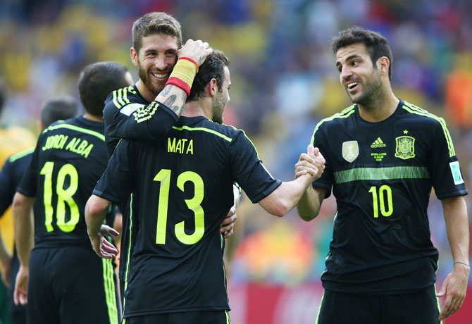 Juan Mata of Spain (centre) celebrates scoring his team's third goal with teammates Sergio Ramos (left) and Cesc Fabregas