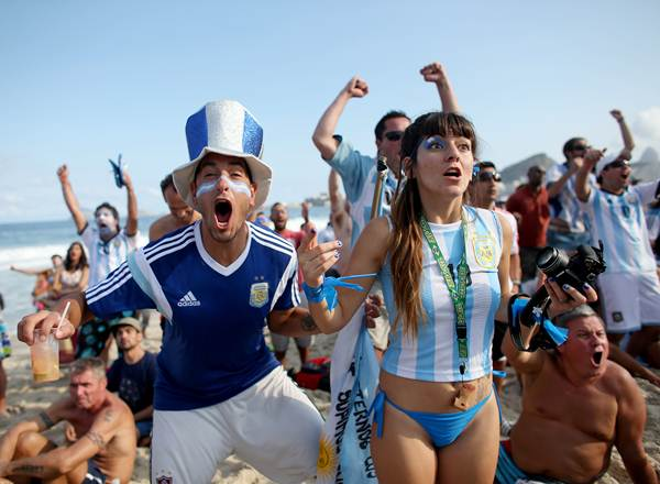 Argentine soccer team fans react to their team scoring against the Iran team as they watch on the screen set up at the Word Cup FIFA Fan Fest during on Copacabana beach.