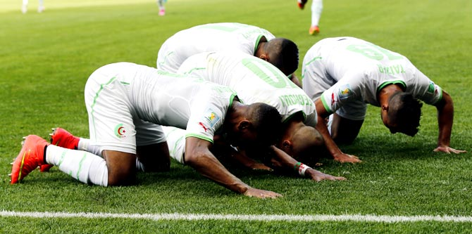 Algeria's Sofiane Feghouli (centre) celebrates with teammates after scoring against Belgium.