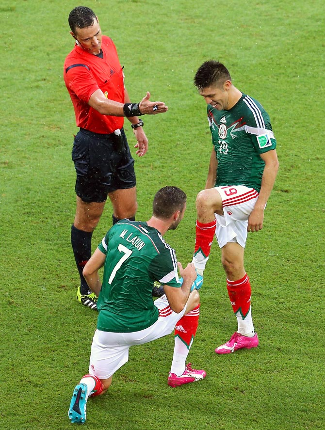 Oribe Peralta of Mexico (R) celebrates his goal with teammate Miguel Layun as referee Wilmar Roldan gestures