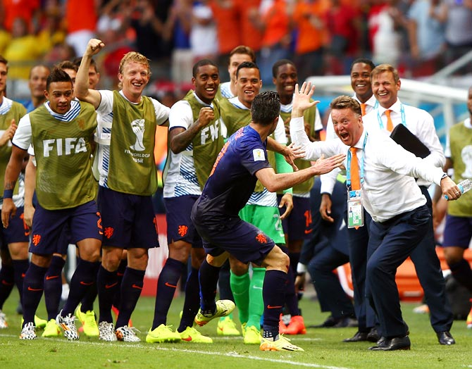 Robin van Persie of the Netherlands (centre) celebrates with head coach Louis van Gaal after scoring the first goal against Spain.