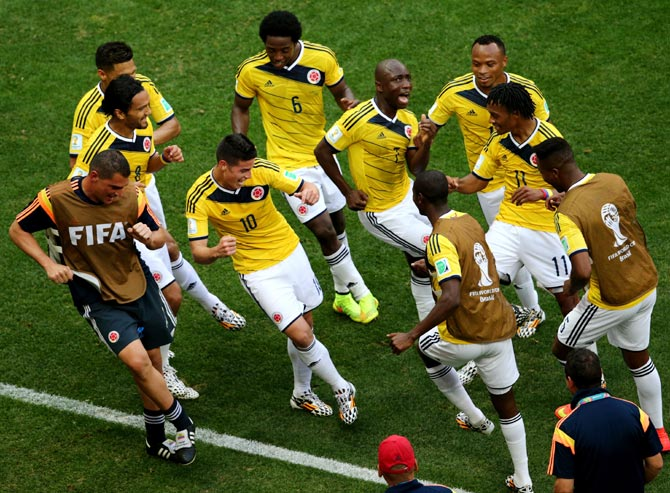 James Rodriguez  (No. 10) of Colombia celebrates by dancing with teammates after scoring his team's first goal against Ivory Coast