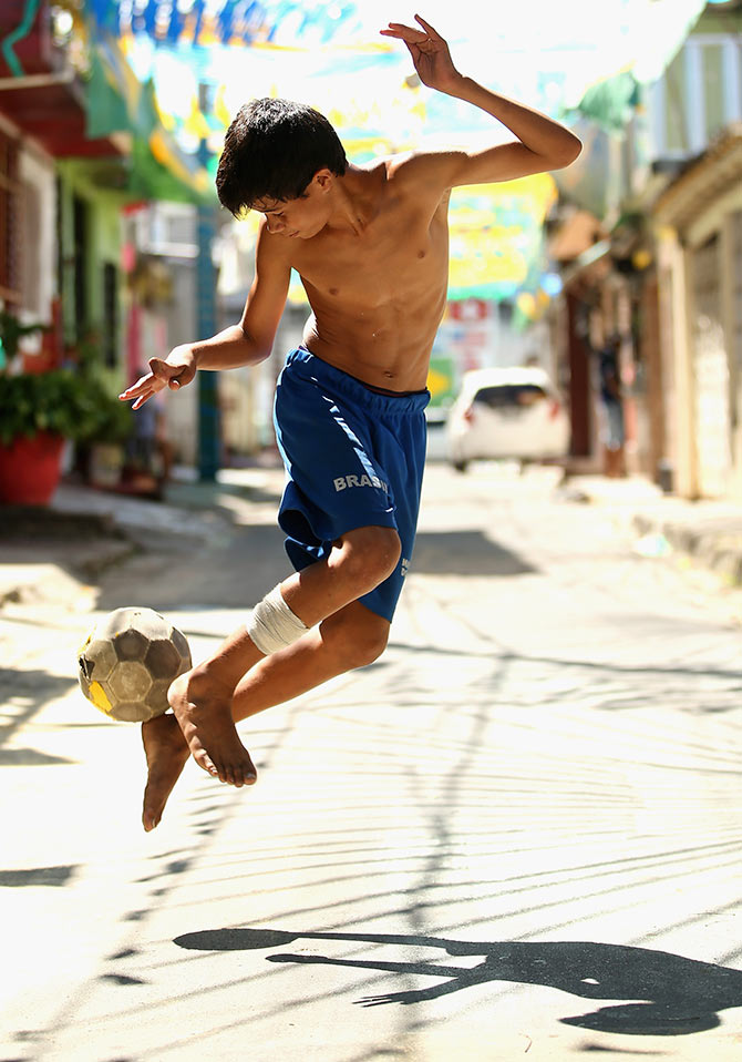 A young boy plays football on the streets in Manaus, Brazil.