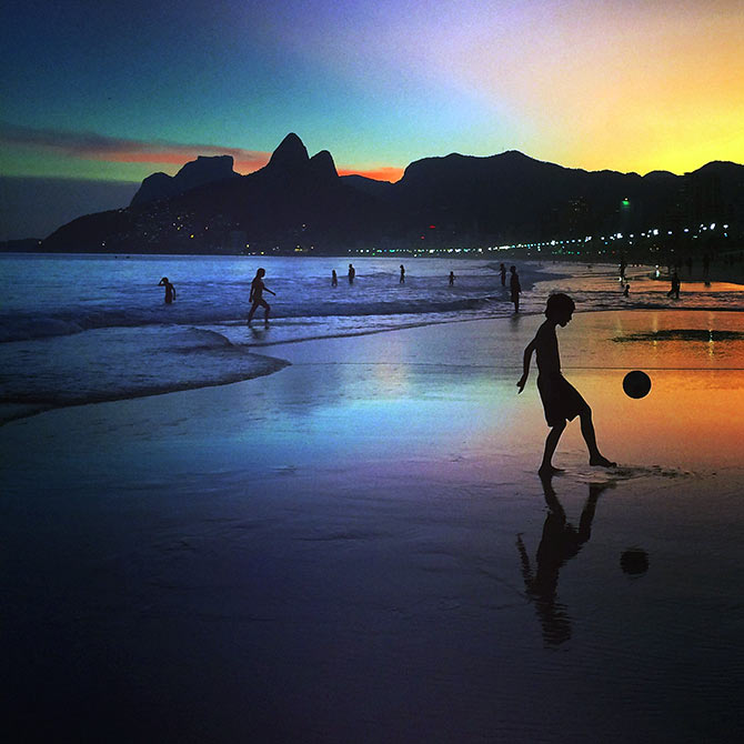 A young boy plays football at sunset on the beach in Rio de Janeiro.