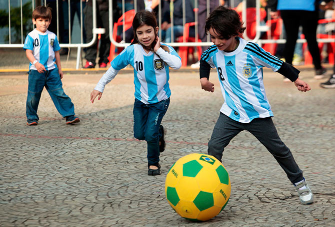 Children wearing Argentina jerseys play soccer at a FIFA public viewing area in Sao Paulo.