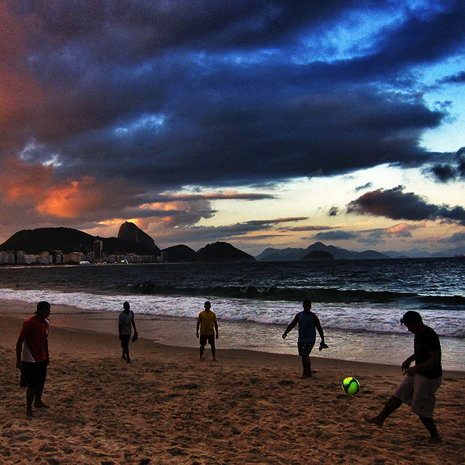 Beachgoers play football on Copacabana Beach in Rio de Janeiro.