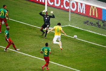 Brazil's Fred scores his team's third goal with a header past Charles Itandje of Cameroon