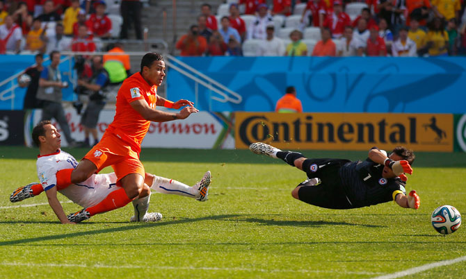 Memphis Depay of the Netherlands shoots and scores his team's second goal past goalkeeper Claudio Bravo of Chile