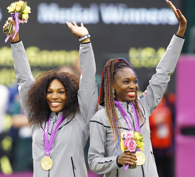 Serena Williams,left, and her sister Venus Williams, of the US, wave with their gold medals during the presentation ceremony for the women's doubles tennis at the All England Lawn Tennis Club during the London 2012 Olympic Games