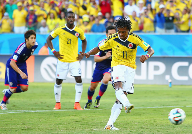 Juan Guillermo Cuadrado of Colombia shoots and scores his team's first goal on a penalty kick