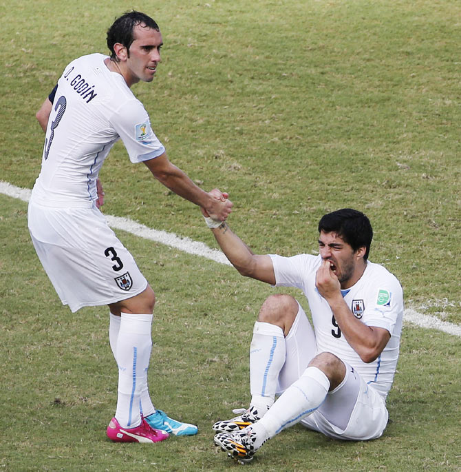 Uruguay's Luis Suarez (R) holds his teeth while sitting on the ground as teammate Diego Godin helps him up during their match against Italy at the Dunas arena in Natal on Tuesday