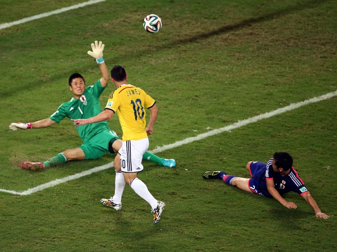 James Rodriguez of Colombia shoots and scores his team's fourth goal past goalkeeper Eiji Kawashima of Japan.