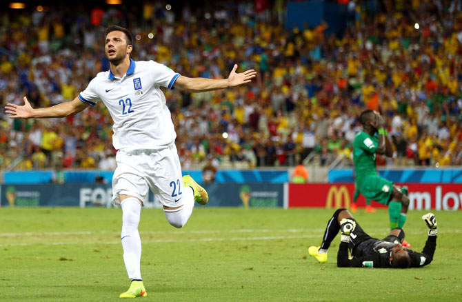 Andreas Samaris of Greece celebrates scoring his team's first goal past goalkeeper Boubacar Barry of the Ivory Coast