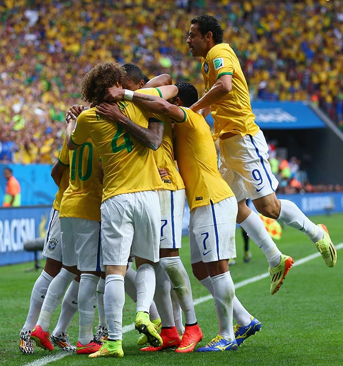 Brazil's players celebrate after Neymar scored the first goal against Cameroon