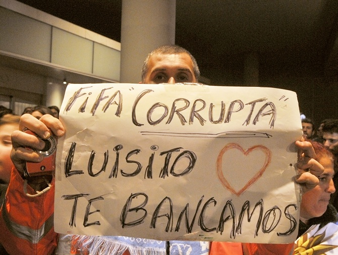 A Uruguay's fan shows a sign in solidarity withLuis Suarez. Sign reads 'FIFA corrupt - Luis, we love and back you'