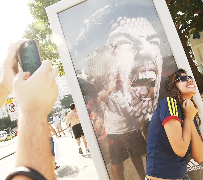 A woman takes a photo next to an advertisement featuring Uruguay's Luis Suarez, mocking the biting incident against opponent Giorgio Chiellini